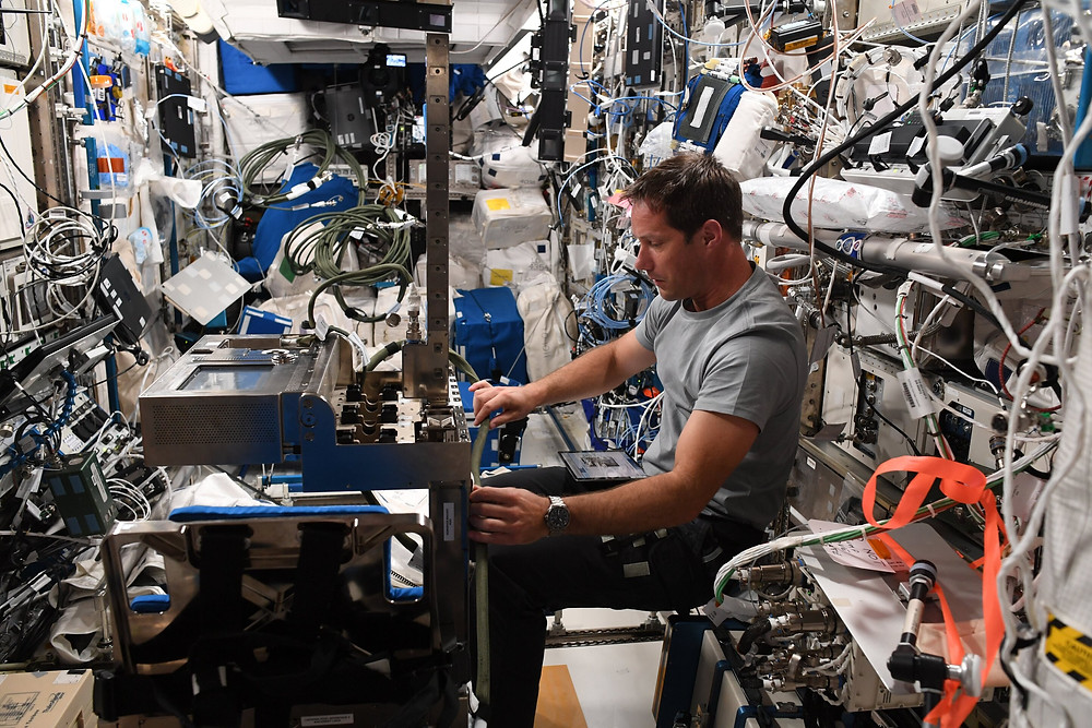 """ESA astronaut Thomas Pesquet configures equipment for an experiment called GRIP that studies astronauts' perception of mass and movement and how they interface with the human body and change in microgravity. Thomas recently shared this image on his social media channels saying: """"An old friend of mine: the ESA GRIP experiment. On my first parabolic flight in 2010, we took part in a safety analysis of the hardware, then during my first flight in 2017 I performed the on-orbit commissioning. It has been going strong since with 6 subjects (including ESA astronauts @astro_alex_esa and @astro_luca), and I should be one of the last ones! It is complex, with lots of cables… always hard to manage when you're free-floating. The experiment is under the responsibility of CADMOS, the French User Operations Centre based in Toulouse. They do an excellent job of sorting out the cables and telling us what goes where."""" Credit: ESA/NASA - T.Pesquet"""