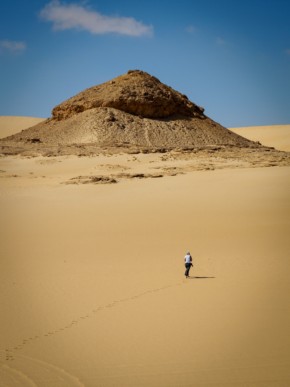Person walks alone in desert.