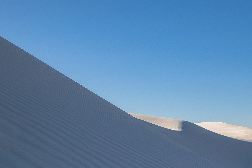 White striped dunes below bright blue sky