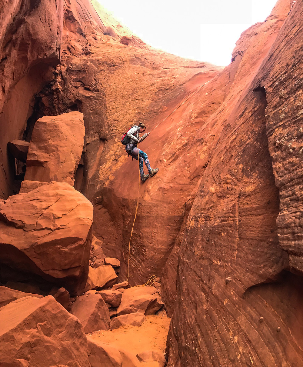 Girl rappelling down a sandstone wall