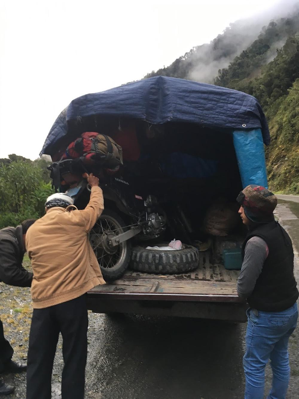 Peruvian men helping lift a motorcycle into a car.