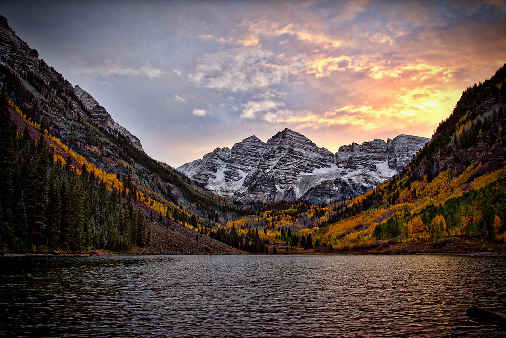 Snowy mountains and golden aspens at sunset