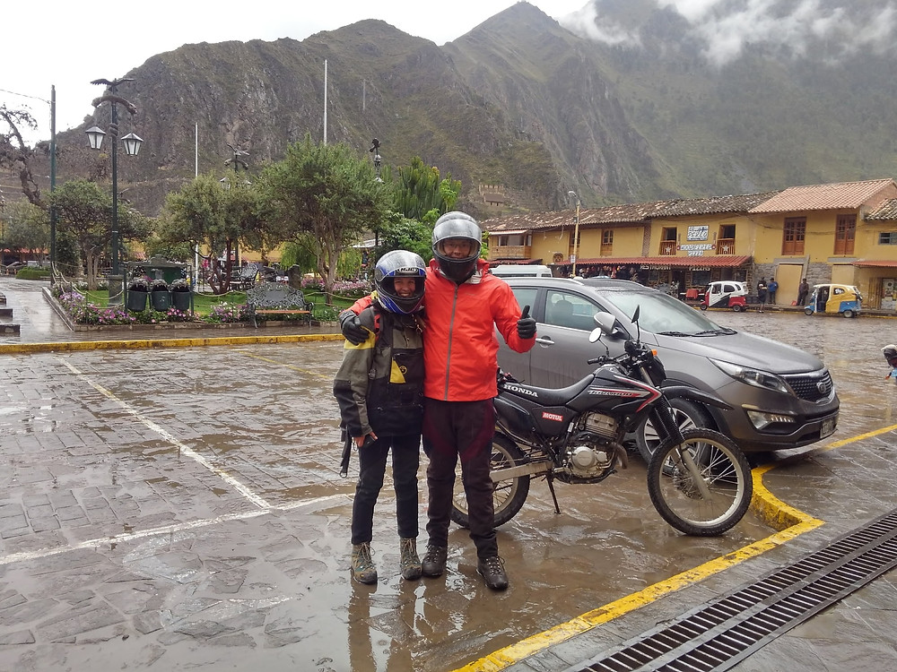 Two people in front of motorcycle in rain.