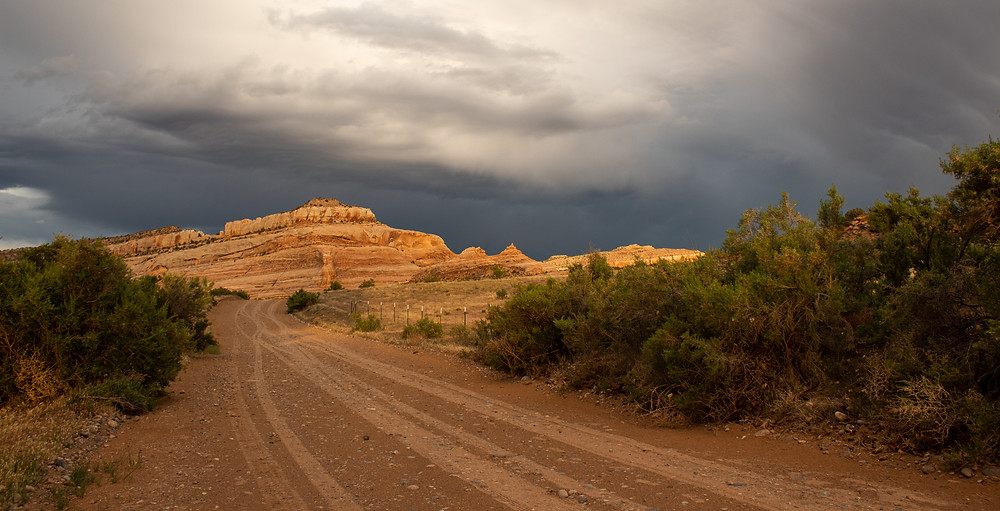 Desert dirt road at sunset