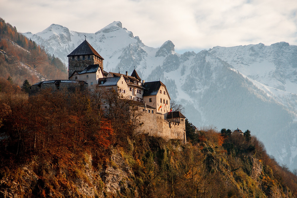 Historic castle on a hill surrounded by mountains.