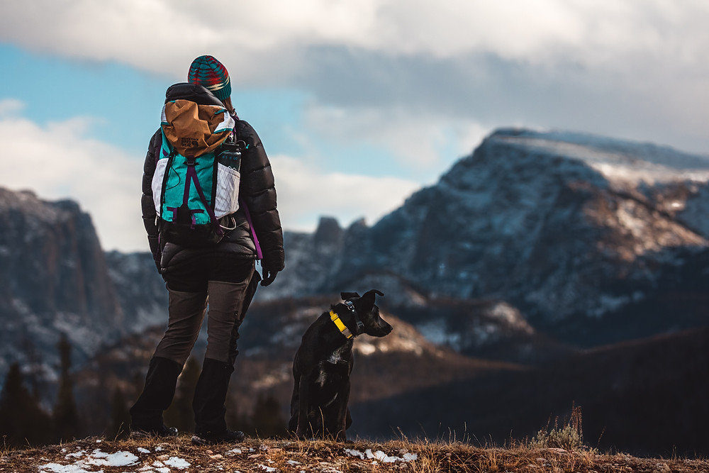 Hiker with black dog on mountain top
