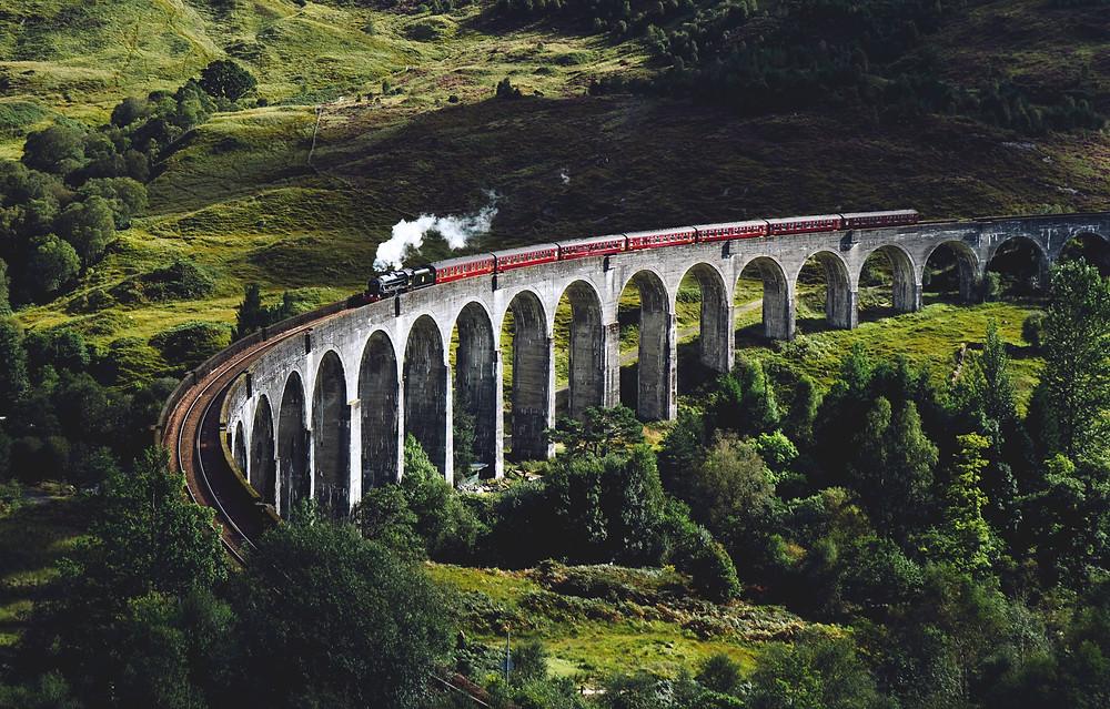 Historic train crossing large bridge in Scotland