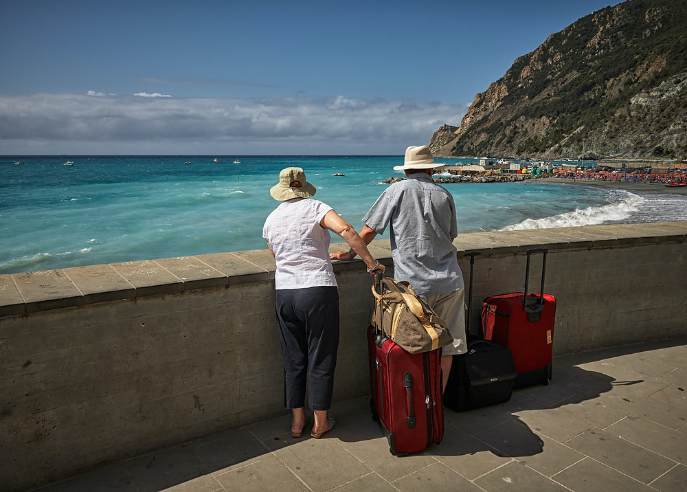 Two tourists with suitcases by coast
