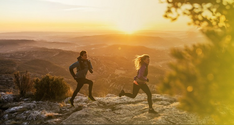 Two people running in the mountains at sunrise