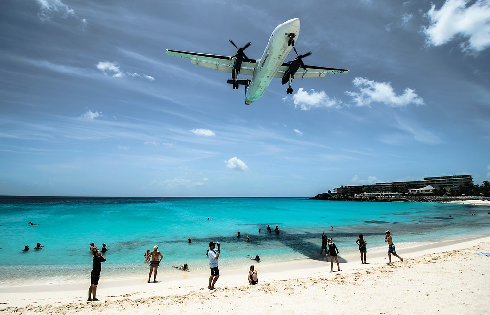Low flying plane over tropical beach.