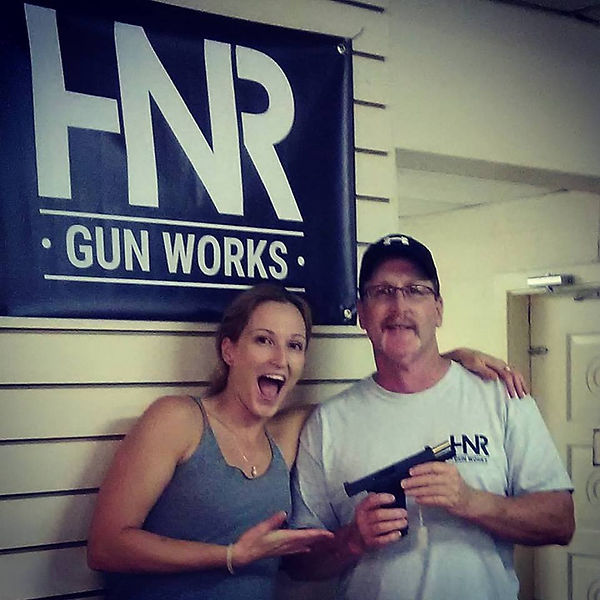 Woman And Man Siiling Holding Custom Gun