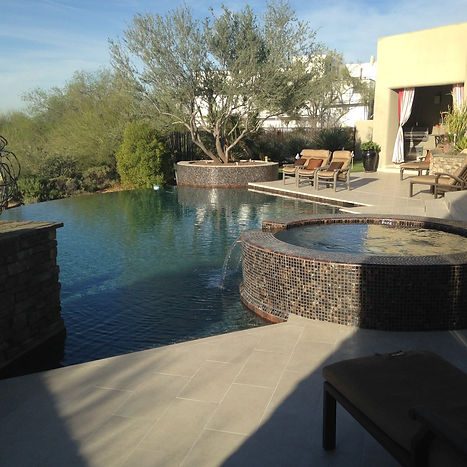 An All Tile Spillway cascades into a Pebble Tec Tropical Breeze Pool. This Negative Edge Pool has raised spa and tile fascia.