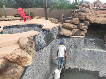 Swimming Pool Service & Repair in Scottsdale installing pool waterline tile a chipped out pool. Next step is Pebble Sheen Surface.