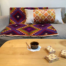 テーブルの上にあるコーヒーとお菓子とソファの上にあるキリム