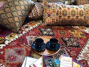 テーブルの上にコーヒーとお菓子とソファの上にあるキリム