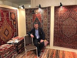 キリムに囲まれて座っているデザイナーのジハン