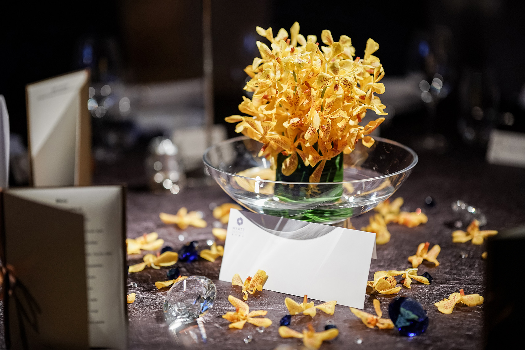 Yellow flower centerpiece with petals on event table