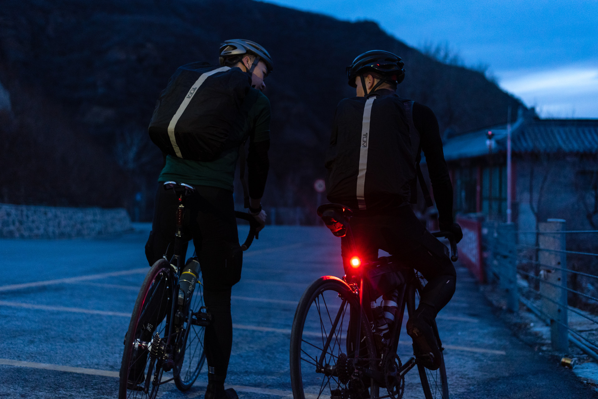 2 cyclist with TUMI backpacks at night in temple