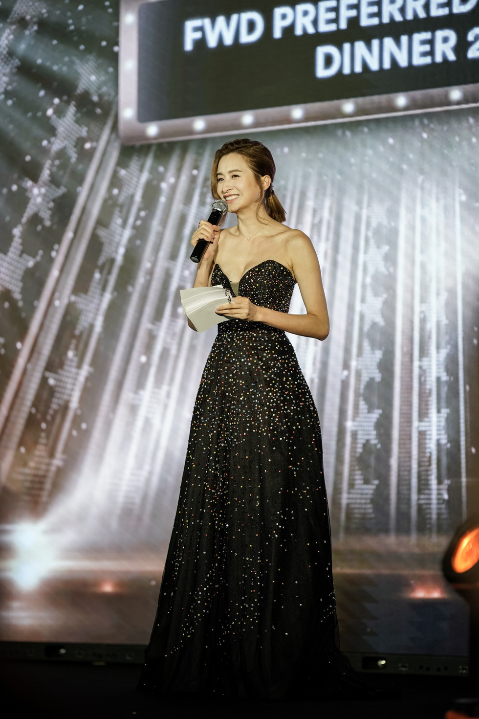 Asian female MC in black dress announcement on stage
