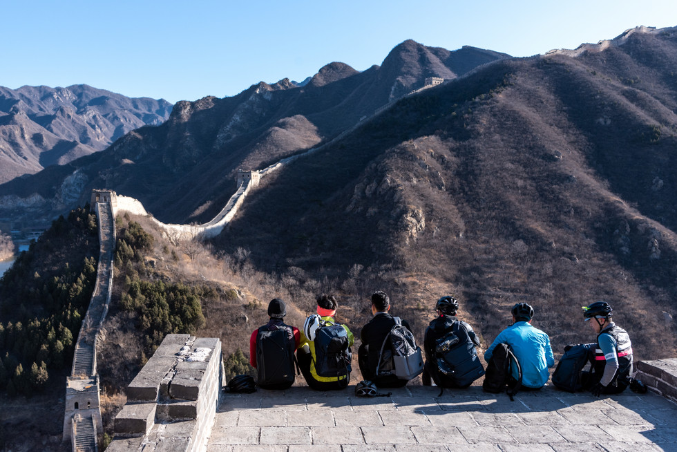 6 asian cyclist with TUMI backpacks on top of the great wall of China