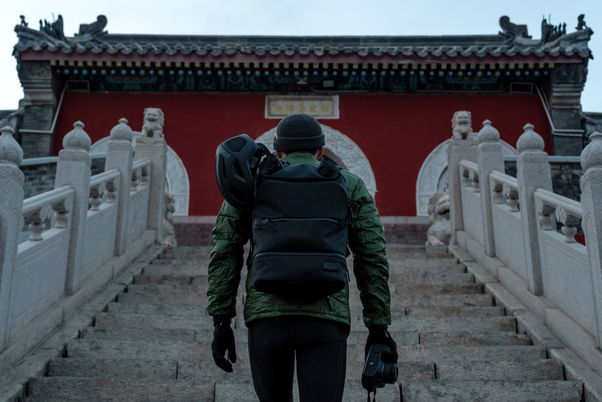 Asian men with TUMI backpack facing an ancient Chinese temple