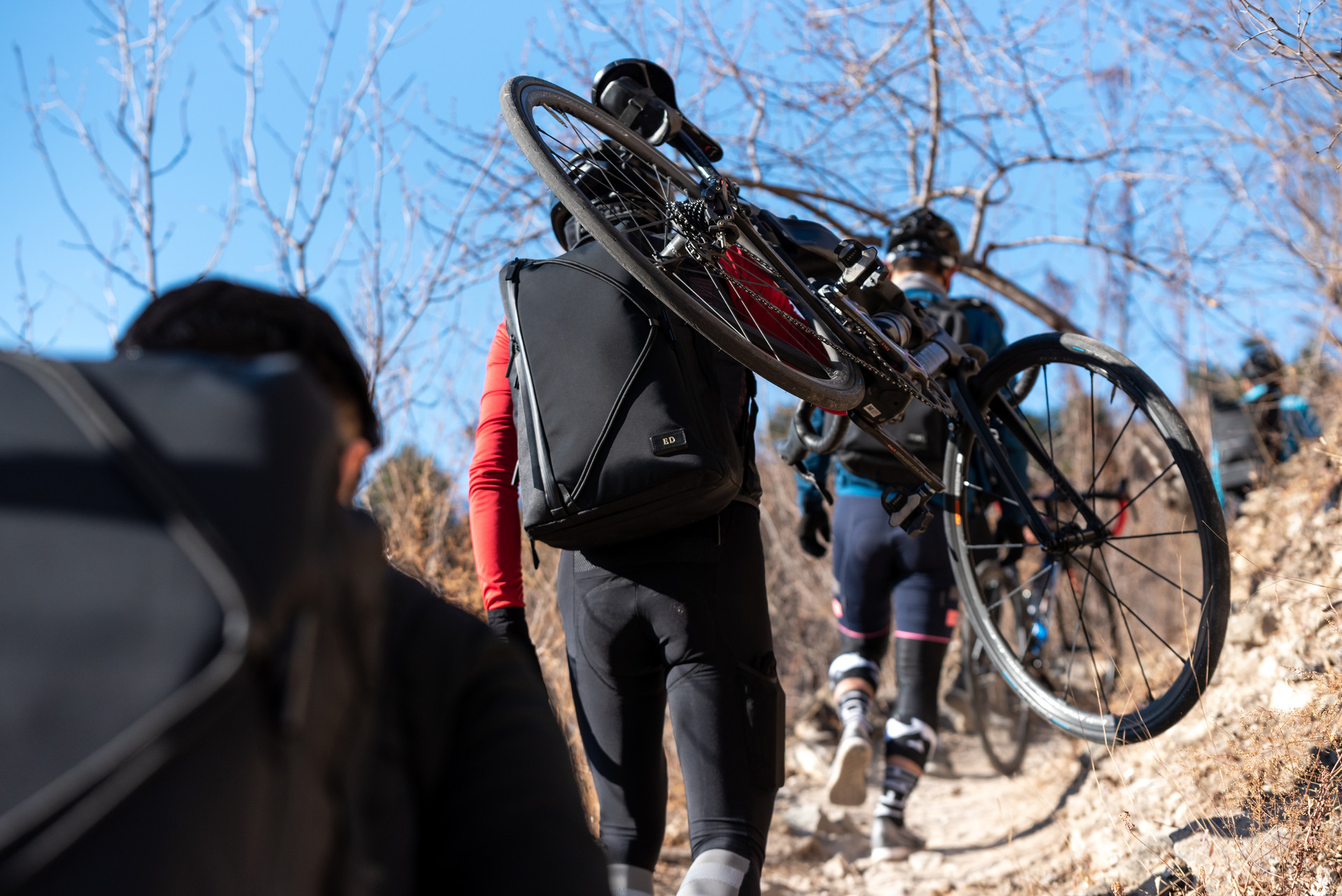 Cyclists with TUMI backpack carrying bicycles up a mountain