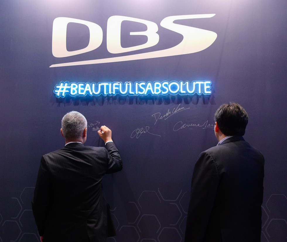 Two men writing their signature in the Aston Martin DBS event sigboard in Hong Kong
