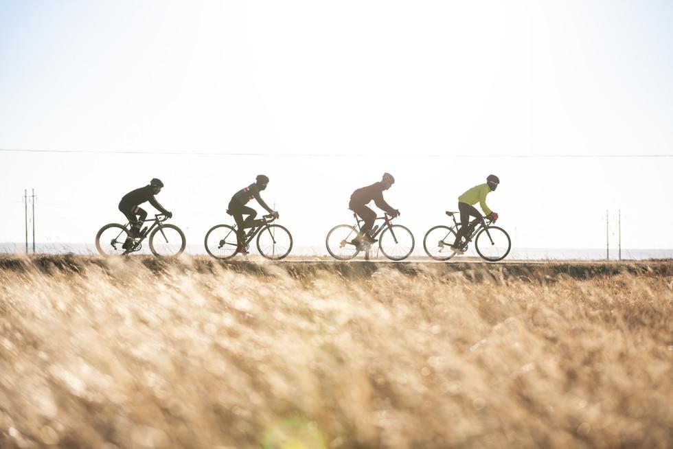 four cyclist riding through a grassy field