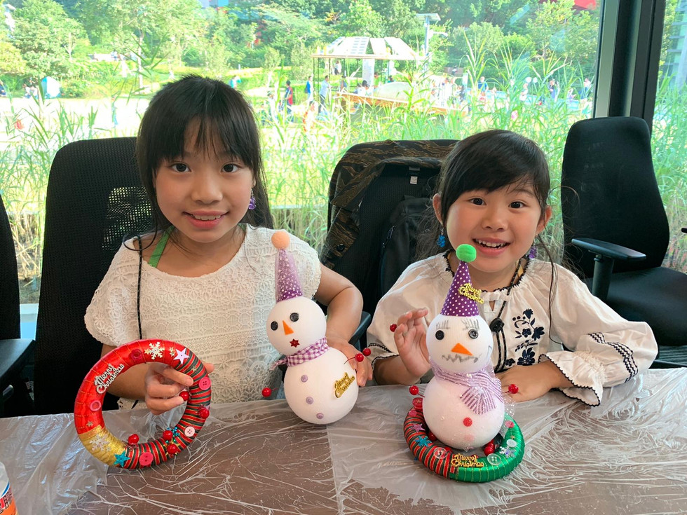 2 young asian girls showing DIY snowman arts and craft
