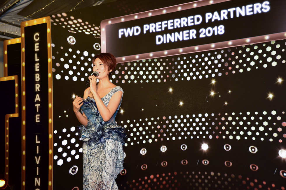 Asian women in blue dress in front of LED wall for annual dinner