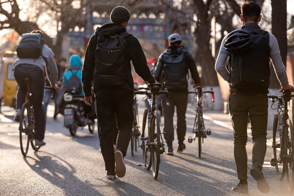 cyclist with TUMI backpacks walking in Beijing China