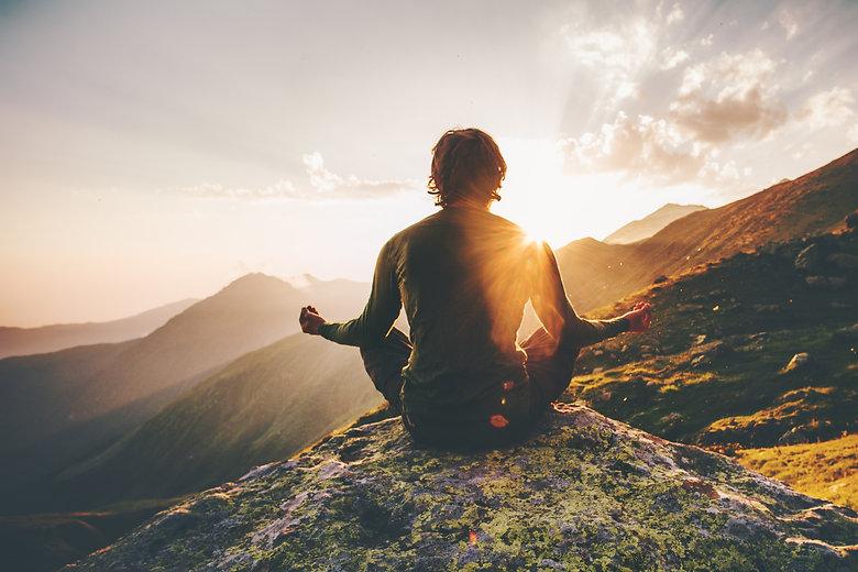 Man meditating yoga at sunset mountains Travel Lifestyle relaxation emotional concept adventure summ