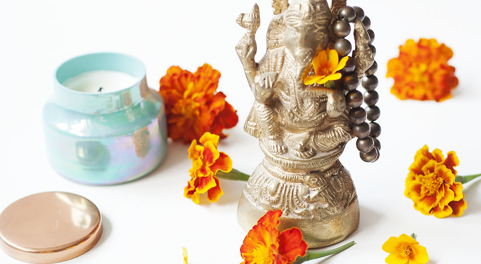 Ganesha figurine with marigolds and a candle in a turquoise jar.jpg