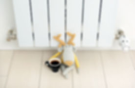Knitted deer sits on the radiator with a