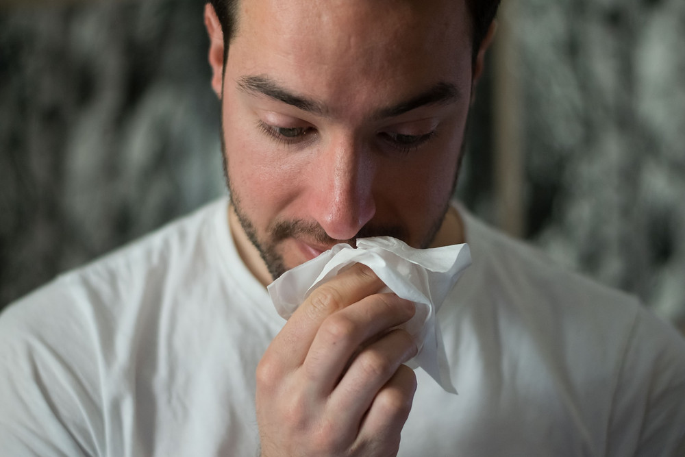 man wiping nose, what are the symptoms of mold exposure