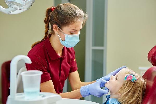 Dentista Pediatra examinando niña