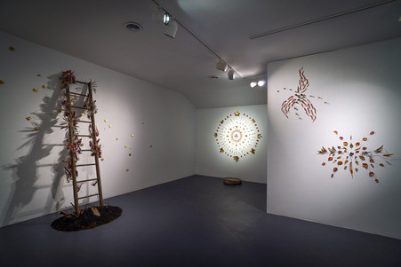 """Descent of the Holy Spirit Installation view  In the photo also seen: Jason Jenn's """"Angels Gale Leaf Mandalas"""" (right)  2021 Wooden ladder, Shoe mold, Glass jars, Handmade origami stars (made of old maps, painted with acrylic), acrylic on paper, rope, various found bird feathers, baked soil from Angels Gate location. 10' x 4' x 4'"""