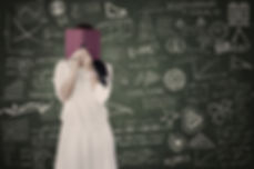 Student behind a book, infront of a blackboard