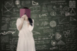 Image of a girl searching in a book, with a background of analyses on a blackboard