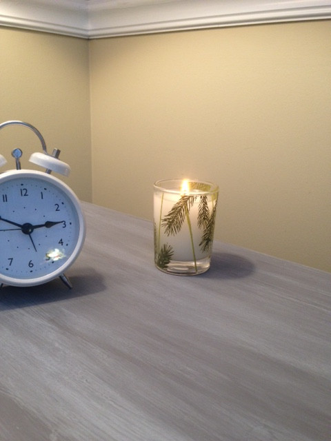 Fresh white fir scented candle burning bright by a small white clock.