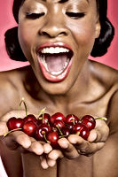Cheerful young woman looking at cherry i