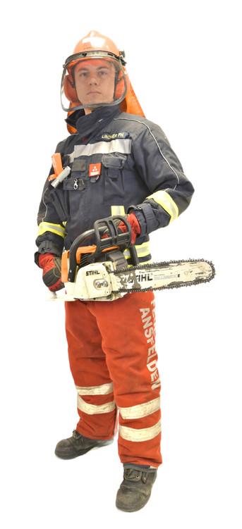 Feuerwehrmann ausgerüstet mit einer Scnitshutzhose, Forsthelm und einer Motorsäge
