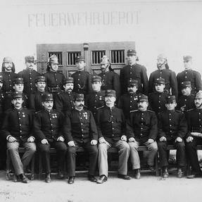 Feuerwehrmannschaft vor dem Feuerwehrhaus