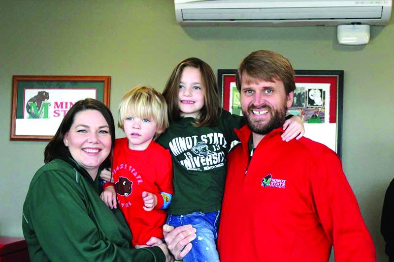 Minot State President Steven Shirley (right) and his family (from the left) Jennifer, William, and Anna pose for a family photo in a Herb Parker Stadium suite during a home football game earlier this month