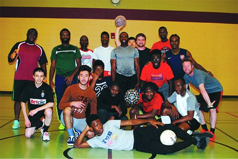 Men's Soccer Club members pose for a picture following a scrimmage.  The club meets every Friday evening at the Wellness Center.  Photo by Tu Tong