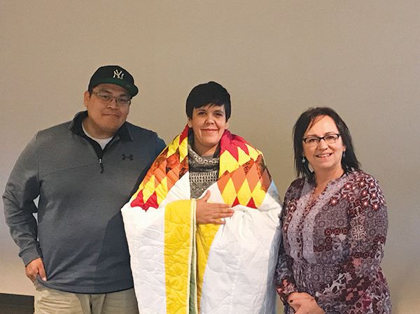 "Melissa Olson (center) accepts a quilt from Helaman Hale (left), MSU Native American Cultural Awareness Club president, and Annette Mennem, Native American Center director.  Olson, co-writer and co-producer of the audio documentary ""Stolen Childhoods,"" spoke on campus last week.  In the documentary, Olson and three other Native women tell the stories of their mothers' adoptions into white families.  The quilt was presented as a thank you for sharing."
