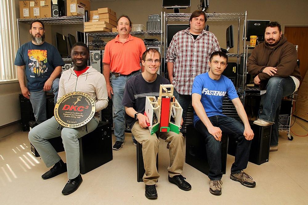 MSU students (from the left) Robert Simpson, Saliou Daillo, Scott Kast (faculty), Deniis Urhmacher, Darren Seifert (faculty), Hayk Margaryan, and Kenneth Kulling pose with trophy