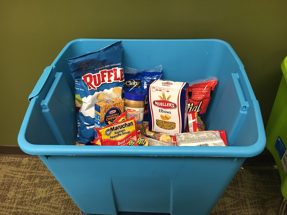 A bin filled with various food items sits in conference room in Wellness Center