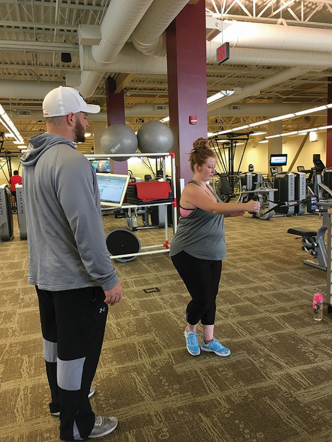 Student trainer Brody Myers, a senior corporate fitness major (left) works with freshman Brooke Collins.  The training sessions are part of the personal training methods class.