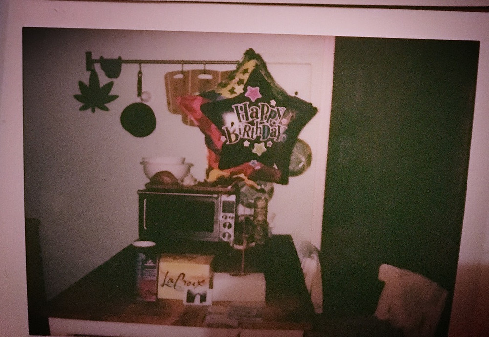 Photograph of Happy Birthday Balloon and assortment of gifts.